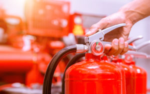 Still of hand pressing on the lever of a fire extinguisher to prepare for fire protection with other fire extinguishers lined up in the back.